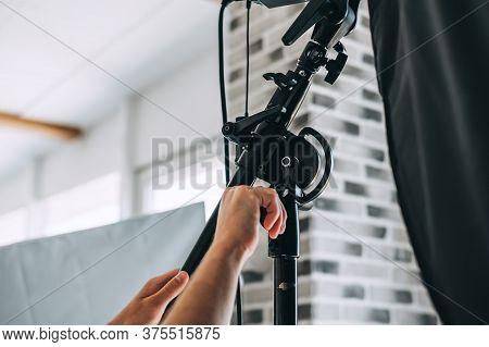 Man Adjusts Lighting Equipment In A Photo Studio, Close-up. High Quality Photo