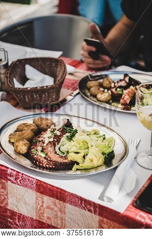 Traditional Portuguese Grilled Octopus, Boiled Potato And Cabbage In Cafe