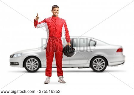 Full length portrait of a car racer in front of a silver car showing thumbs up isolated on white background