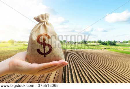 A Hand Holds Out A Dollar Money Bag On A Background Of A Farm Field. Lending Farmers And Agricultura