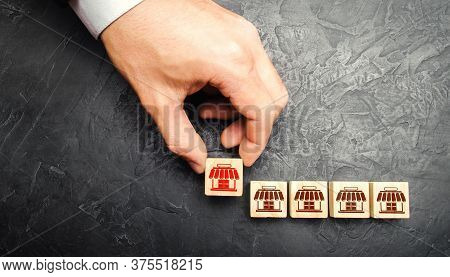 Man Adding A Block With A Store Icon To Others. Franchise Commercial Concession Concept. Investing I