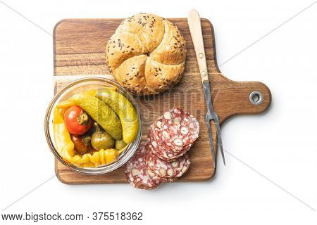 Sliced italian salami with hazelnuts, pickled chili peppers and pickles isolated on white background.