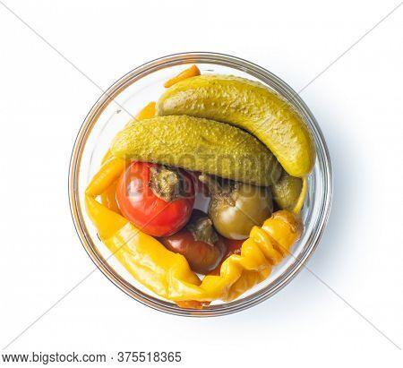Pickled chili peppers and pickles in bowl isolated on white background.