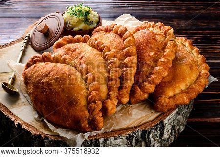 Russian Patties Pasties, Hot Cakes, Pirozhki, Pies On Wooden Cupboard . Traditional Homemade Fried P