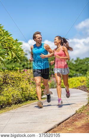 Active runners couple running talking happy training buddy outside workout outdoors in summer park. Woman and man jogging healthy cardio workout lifestyle.