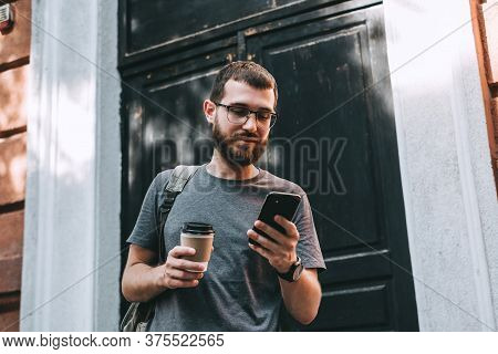 Smiling Young Bearded Man With Backpack Using Smartphone While Standing Outdoors At The City Street