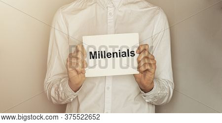 Man Take A Paper With Text Millenials On The Shirt With Office Background