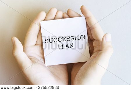 White Paper With Text Succession Plan In Male Hands On A White Background