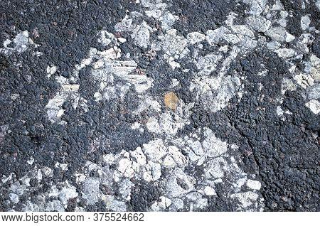 Semi-destroyed Granular Asphalt, Old Technology Of Road Production. Sidewalk, Roadway Close-up