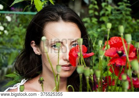 Sexy Girl With Poppy Seed Flowers. Beauty And Perfection. Summer Flower Green Garden. Beautiful Girl