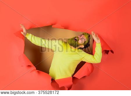 Smiling Bearded Man Looking Through Paper Hole. Advertising. Discount. Sale. Copy Space For Advertis
