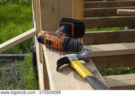 Cordless Screwdriver And Hummer Against The Background Of Boards