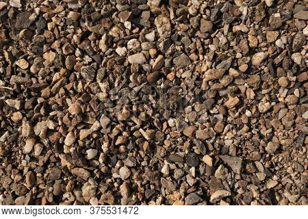 Small Stones, Pebbles On The Ground. Texture. Brown Background