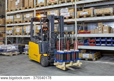 St. Petersburg, Russia - December 24, 2018: Industrial Warehouse With Shelving System. A Forklift Tr