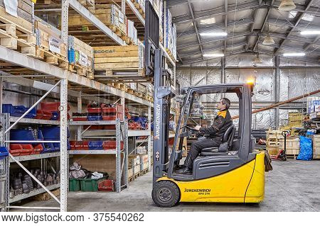 St. Petersburg, Russia - December 24, 2018: A Forklift Truck Removes A Pallet Of Goods From A Rack I