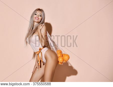Beautiful Sexy Woman On Sport Diet Hold Orange Fruits. Weight Loss Healthy Eating Control With Tape