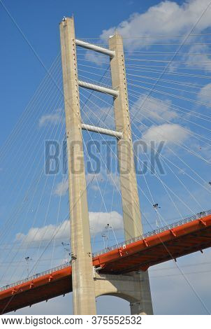 The Red Roadway Of A Bridge Is Supported By A Vertical Pylon With Multiple Metal Struts. The Sky Is