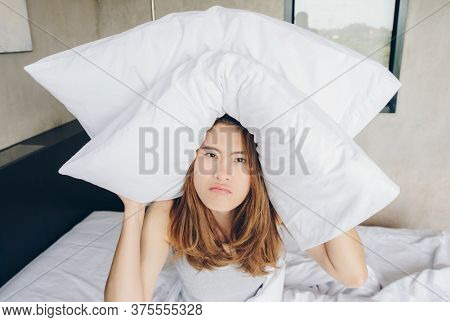 Young Beautiful Asian Woman Hates Waking Up Early In The Morning. Sleepy Girl Holding The Pillow On