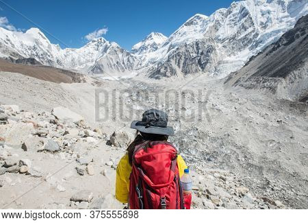 Back View Of Woman Tourist Looking To The Beautiful View Of Himalayas Mountain Range And Khumbu Glac