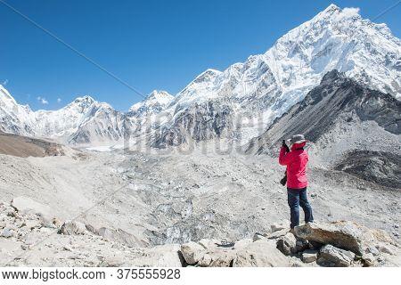 Woman Tourist Taking Photos Of Beautiful Himalayas Mountain Range And Khumbu Glacier During Trekking