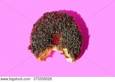 Donut. Cake Donut with Chocolate Frosting and Chocolate Sprinkles. Donut with bite taken out on a pink background.