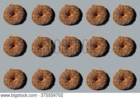 Donut. Cake Donut with Chocolate Frosting and Chocolate Sprinkles. Donut Art. Repeating Doughnut pattern. Backgrounds and Wallpapers.  Gray Background.