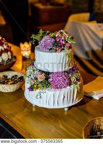 Beautiful Delicious Wedding Cake In Many Tiers With Fresh Wild Flowers And Roses