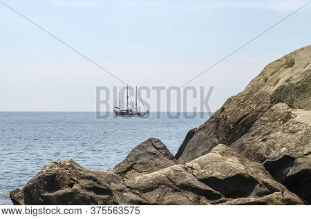 Rock In The Sea And A Three-masted Sailboat On The Horizon