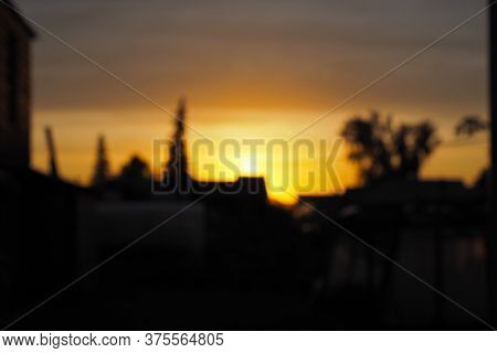 Blurred Background: Sunset In The Village. The Yellow Sun Set Behind One-story Houses. Dark Backdrop