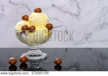 Bowl Of Vanilla Flavor Ice Cream Sundae With Chocolate Candy With Copy Space