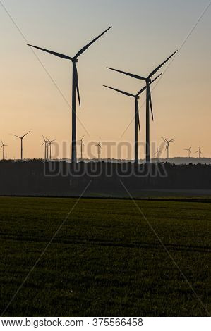Black Silhouette Of Windturbines Energy Generator On Amazing Sunset At A Wind Farm In Germany