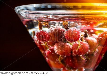 Glass Of Cold Refreshing Summer Drink With Berries And Ice Cubes On Table Close Up.refreshing Summer