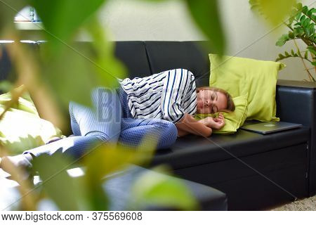 Tired Young Woman Lies On Sofa At Home, Taking A Nap After Work, Relaxing At Home During The Day