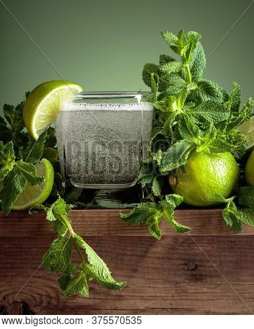 Carbonated Drink Or Cocktail With Lime Slices And Mint On A Old Wooden Table. Green Background.