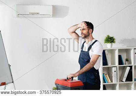 Workman Touching Forehead While Standing With Toolbox Near Broken Air Conditioner And Suffering From
