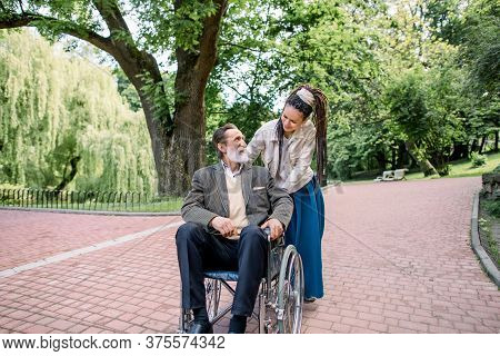 Disabled Senior Bearded Man In Wheelchair And His Creative Girl Assistant With Dreadlocks, In Hipste