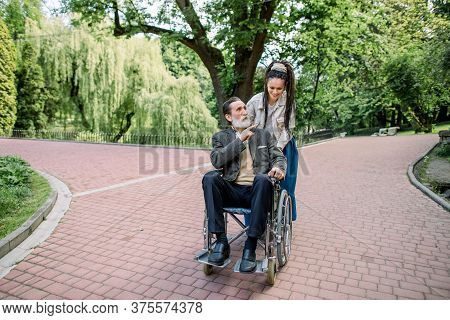 Happy Young Hipster Modern Woman With Dreadlocks, Walking Together With Her Old Senior Grandfather,