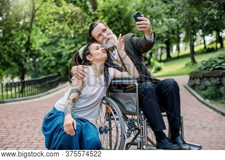 Hipster Girl With Long Dreadlocks And Handsome Bearded Senior Man Grandfather In Wheelchair At Park