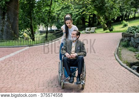 Attractive Young Hipster Woman With Long Hair Dreadlocks, Care Giver Or Social Worker, Pushes Wheel