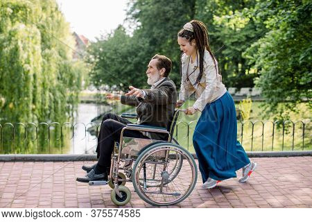 Pretty Hipster Young Woman With Dreadlock Hair Pushing Wheelchair With Elderly Man, Having Fun In Th