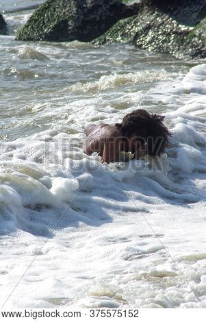 Solitary Young Boy Laughs While Playing In The Ocean Waves. High Quality Photo Shot In Natural Light