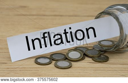 Inflation Word On A White Strip Of Paper With A Can Of Money. Business And Finance Concept.
