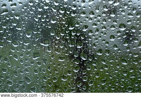 Rain Drops On Window Glasses Surface With Cloudy Background . Natural Pattern Of Raindrops On Cloudy