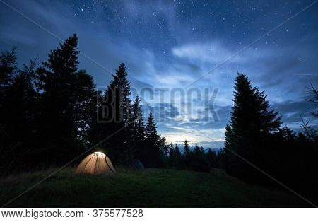 Magnificent View Of Night Blue Sky Over Meadow With Illuminated Camp Tent. Fantastic Scenery Of Tour