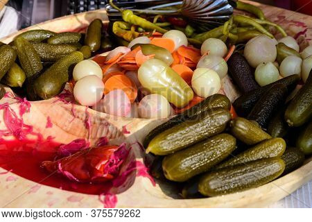 Mixed Pickles On A Wooden Table For Sale At A Food Market With Pickled Cucumbers, Red And Green Hot
