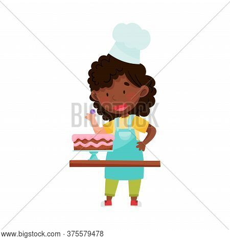 Little African American Girl Character In Hat And Apron Standing At Kitchen Table And Decorating Cak