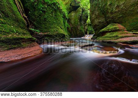 Small River With Red Water Flowing Through Finnich Glen Landscape