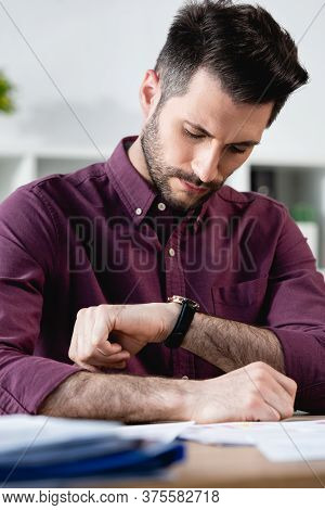 Selective Focus Of Serious Businessman Checking Time At Wristwatch While Sitting At Workplace