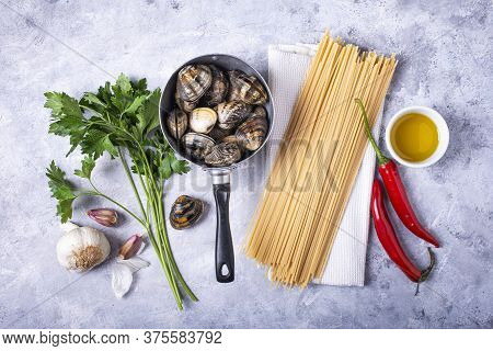 On A Gray Structure Background, In An Old Colander, Fresh Clams With Shell, Spaghetti And Various In