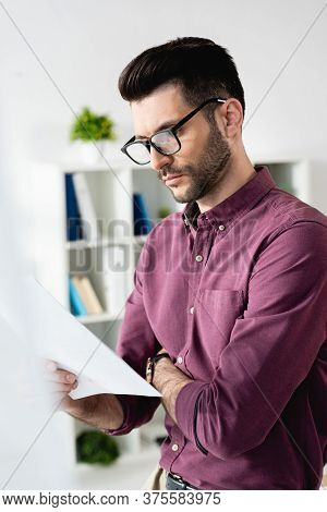 Selective Focus Of Concentrated Businessman In Eyeglasses Looking At Document In Office